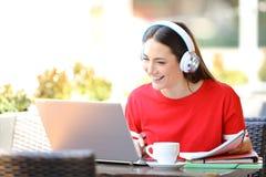 ?tudiant heureux avec l'apprentissage en ligne d'?couteurs avec un ordinateur portable photo stock