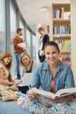 Étudiant heureux dans la bibliothèque d'école Photo stock