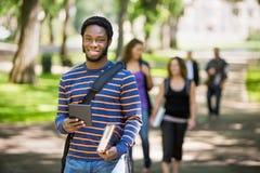 Étudiant heureux Holding Digital Tablet sur le campus Photographie stock libre de droits