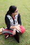 Étudiant indien s'asseyant dans une pelouse d'université et pensant avec un stylo et un livre Photographie stock