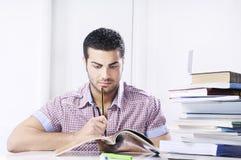 Étudiant inquiété regardant des livres sur le fond blanc Photo stock