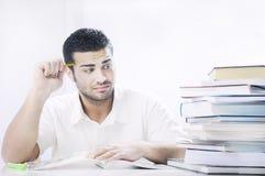 Étudiant inquiété regardant des livres sur le fond blanc Photos libres de droits