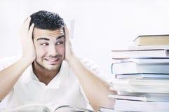 Étudiant inquiété regardant des livres sur le fond blanc Photographie stock libre de droits
