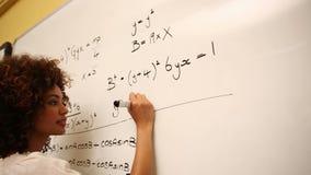 Étudiant intelligent résolvant des problèmes de maths sur le tableau blanc clips vidéos