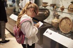 Étudiant Looking At Artifacts au cas où en voyage au musée photographie stock libre de droits