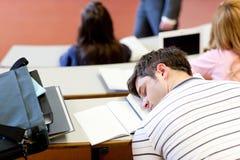 Étudiant mâle en sommeil pendant une leçon d'université photographie stock