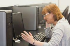 Étudiant mûr contrarié travaillant sur l'ordinateur Image stock