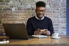 Étudiant masculin à l'aide de la zone de wifi et des dispositifs modernes avec le sourire sur le visage Photo libre de droits