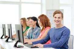 Étudiant masculin avec des camarades de classe dans la classe d'ordinateur Images stock