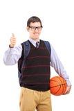 Étudiant masculin avec le sac d'école tenant un basket-ball et donnant thu Images stock