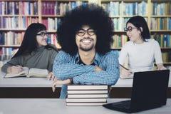 Étudiant masculin avec ses amis dans la bibliothèque Photographie stock