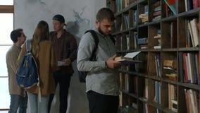 Étudiant masculin choisissant le livre sur l'étagère dans la bibliothèque banque de vidéos