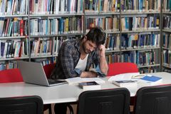 Étudiant masculin confus Reading Many Books pour l'examen photos libres de droits