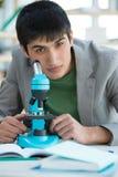 Étudiant masculin dans le laboratoire fonctionnant avec le microscope photo stock