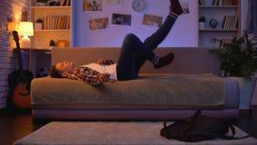 Étudiant masculin de l'adolescence fatigué venant à la maison après des conférences, se couchant sur le divan, repos banque de vidéos