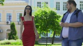 Étudiant masculin de poids excessif regardant la belle femme mince dans la robe rouge, timidité clips vidéos