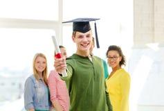 Étudiant masculin de sourire avec le diplôme et le coin-chapeau image stock