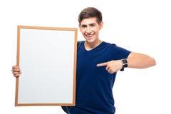 Étudiant masculin dirigeant le doigt sur le conseil vide Image stock