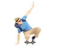 Étudiant masculin enthousiaste avec le cartable patinant sur un panneau de patin Photos libres de droits