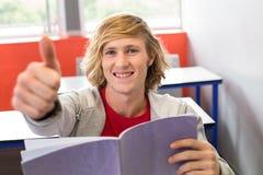 Étudiant masculin faisant des gestes des pouces dans la salle de classe photographie stock