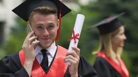 Étudiant masculin heureux parlant au téléphone, recevant des félicitations sur l'obtention du diplôme clips vidéos