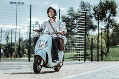 Étudiant masculin optimiste couvrant à l'université sur la motocyclette images stock