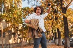 Étudiant masculin ou homme d'affaires réussi heureux avec les cheveux bouclés criant avec l'expression de gain, poings pompés et  image stock