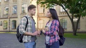 Étudiant masculin parlant avec le bel ami féminin, discutant l'essai près de l'université clips vidéos