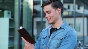 Étudiant masculin Reading Notepad Outdoors à l'université banque de vidéos