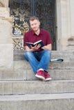 Étudiant masculin Sitting On Steps et lecture en dehors de Bui image libre de droits