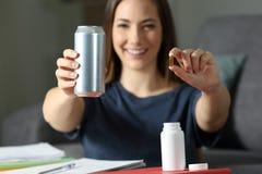 Étudiant montrant des pilules de supplément de boissons et de vitamine d'énergie Images libres de droits
