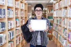 Étudiant montrant l'écran de comprimé dans la bibliothèque Photo stock