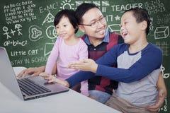 Étudiant montrant l'ordinateur portable sur son ami et professeur Photo libre de droits