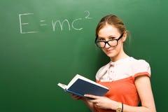 Étudiant par le tableau avec e=mc2 Photo stock