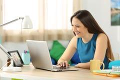 Étudiant recherchant le contenu dans un ordinateur portable dans sa chambre image stock
