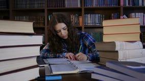 Étudiant recouvert avec des livres autour de et l'écriture dans un carnet 4K banque de vidéos