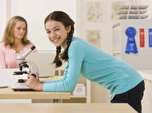 Étudiant regardant dans le microscope dans la salle de classe photos libres de droits