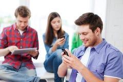 Étudiant regardant dans le smartphone l'école Photo libre de droits