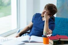 Étudiant regardant par la fenêtre image stock