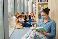 Étudiant s'asseyant à la bibliothèque universitaire avec des amis Photographie stock libre de droits