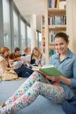 Étudiant s'asseyant dans la bibliothèque d'école avec des amis Photos libres de droits