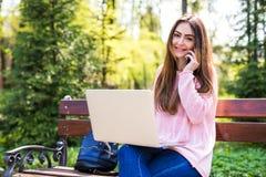 Étudiant s'asseyant sur un banc de parc parlant au téléphone et travaillant sur son ordinateur portable Photos stock