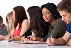 Étudiant sûr s'asseyant avec des camarades de classe écrivant au bureau Photographie stock
