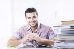 Étudiant souriant avec des livres sur le fond blanc Image libre de droits