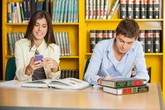 Étudiant Studying While Friend à l'aide du portable dedans Image stock