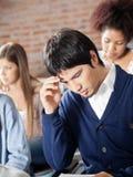 Étudiant Thinking With Classmates dans la salle de classe photos stock