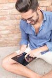 Étudiant travaillant sur sa tablette d'écran tactile Photos stock