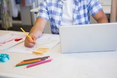 Étudiant universitaire à l'aide de l'ordinateur portable tout en dessinant la photo Photo stock