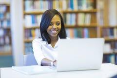 Étudiant universitaire à l'aide de l'ordinateur portatif photographie stock libre de droits