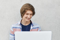 Étudiant universitaire à la mode à l'aide de l'ordinateur portable pour son étude, ayant le sourire agréable tout en causant avec Photographie stock libre de droits